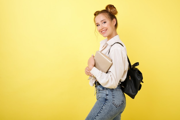 Studente con libri e zaino su uno spazio giallo