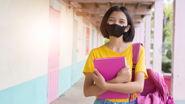 Studente con maschera facciale a scuola indossa una maglietta gialla