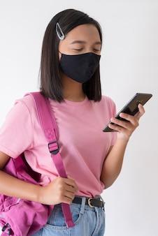 Studente con maschera per il viso con smartphone indossa la camicia rosa