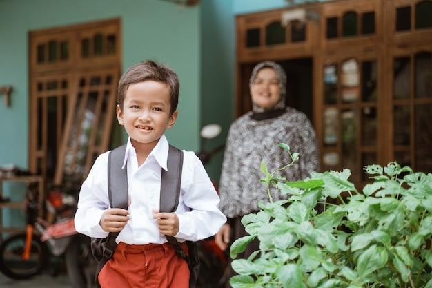 Studente con l'uniforme scolastica indonesiana si prepara a scuola la mattina