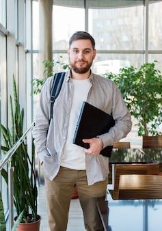 Studente con laptop e zaino vicino alla finestra nel campus universitario riaprire. adolescente caucasico, uomo barbuto sicuro che trasporta laptop in biblioteca. libero professionista in un moderno ufficio di coworking con piante.