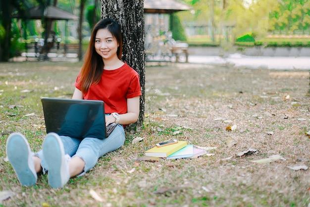Donna dell'allievo che fa un rapporto in un giardino all'aperto con un computer portatile prima del finale di estate