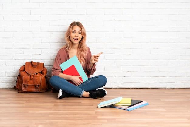 Studente donna con i capelli rosa seduto sul pavimento in interni che punta di lato per presentare un prodotto