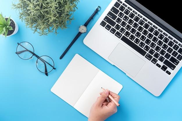 Uno studente scrive sul libro bianco aperto o sulla contabilità isolato su un posto di lavoro blu pulito minimo a casa con lo smartphone e gli accessori, lo spazio della copia, laici piana, vista dall'alto,