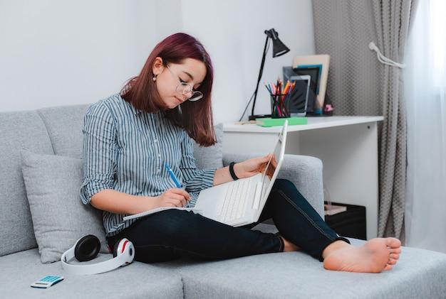 Studente che scrive al divano