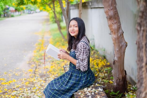 Libro della stretta della ragazza dello studente sotto il bello albero.