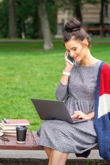 La giovane donna dell'allievo sta parlando dallo smartphone utilizzando il computer portatile sulla panchina nel parco