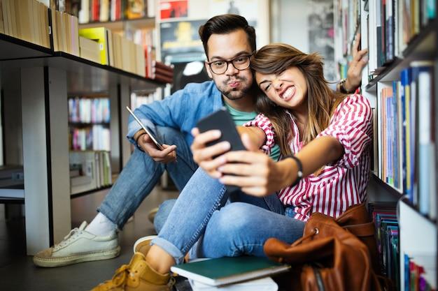 Gli studenti stanno studiando insieme in biblioteca. coppia, studio, tecnologia, educazione amore concetto