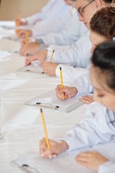 Studenti che frequentano la lezione nella facoltà di medicina e prendono appunti sui quaderni