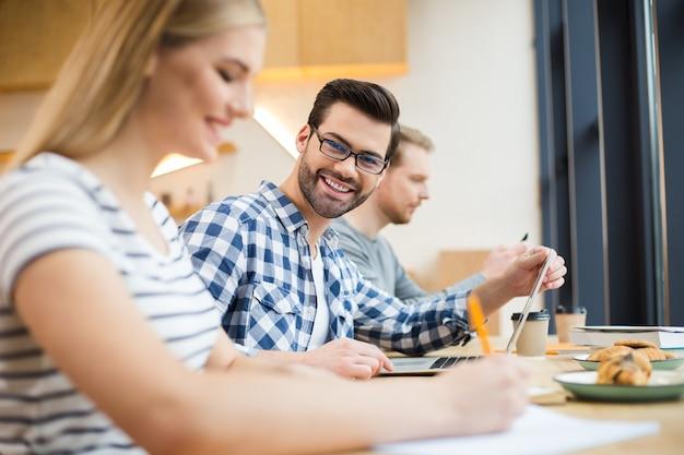 Caffè degli studenti. bel uomo allegro positivo seduto nella caffetteria e ti guarda mentre studia con i suoi amici