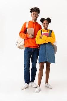 Studenti in abiti colorati in possesso di quaderni, isolati su muro bianco
