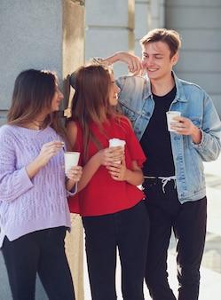 Studenti che si godono una tazza di caffè per andare in strada. giovani che comunicano all'aperto al mattino con una tazza di bevanda energetica