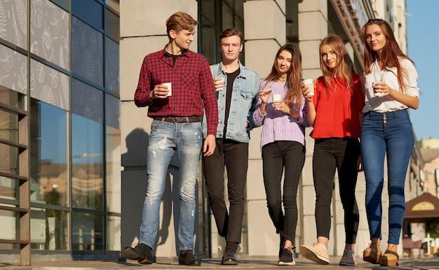 Studenti che si godono una tazza di caffè per andare in strada. i giovani stanno camminando all'aperto con una tazza di bevanda energetica