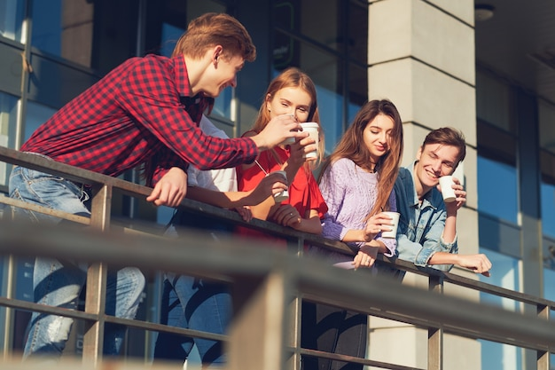 Studenti che si godono una tazza di caffè per andare in strada. giovani al mattino all'aperto con una tazza di bevanda energetica energy