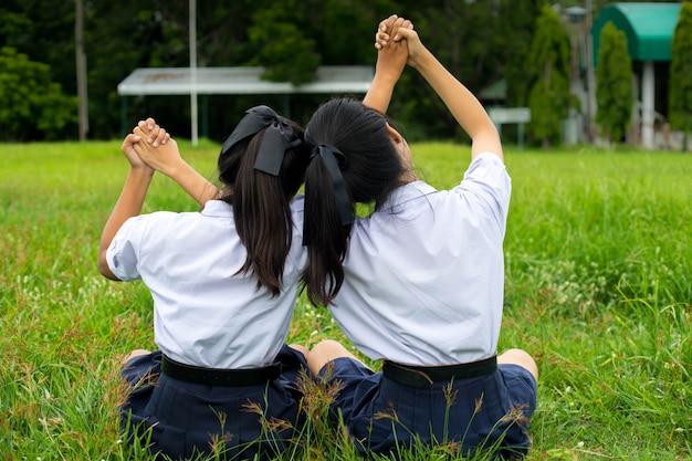La ragazza degli studenti sta abbracciando nel campo, concetto dei migliori amici.