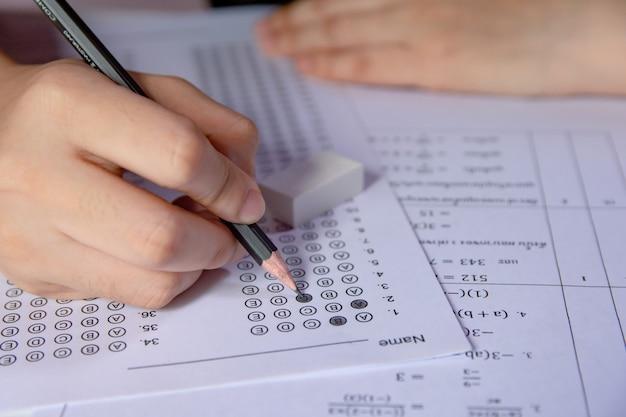 Mano degli studenti che tiene la matita che scrive scelta selezionata sui fogli delle risposte e sui fogli delle domande di matematica. studenti che fanno il test facendo l'esame. esame scolastico
