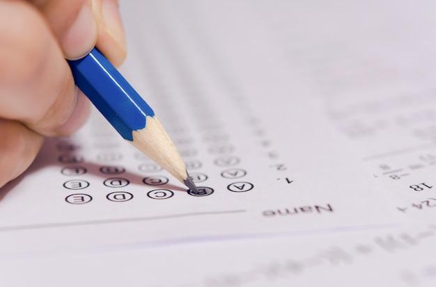 La mano degli studenti che tiene la matita che scrive la scelta selezionata sui fogli di risposta
