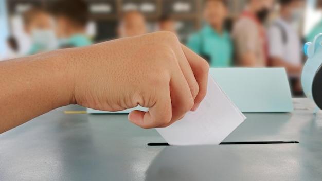 Mani degli studenti che votano nell'urna elettori il giorno delle elezioni per il consiglio studentesco e il consiglio scolastico