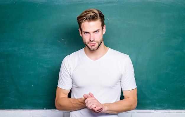 La vita degli studenti torna a scuola informazioni sulla lavagna vuota studente serio alla lavagna uomo