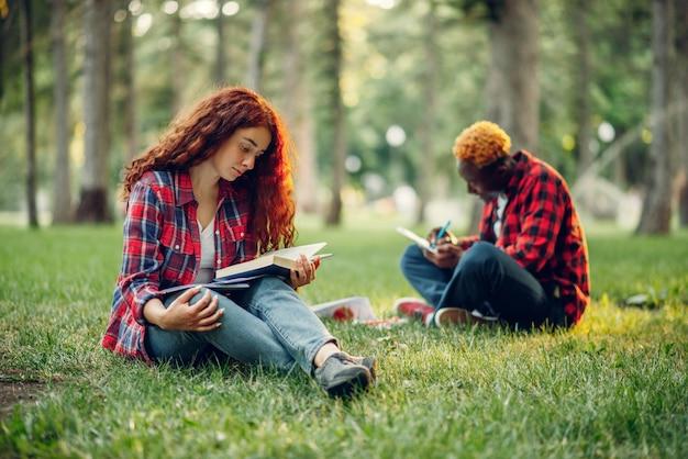 Studenti che leggono un libro sull'erba nel parco estivo. adolescenti maschi e femmine che studiano all'aperto e pranzano