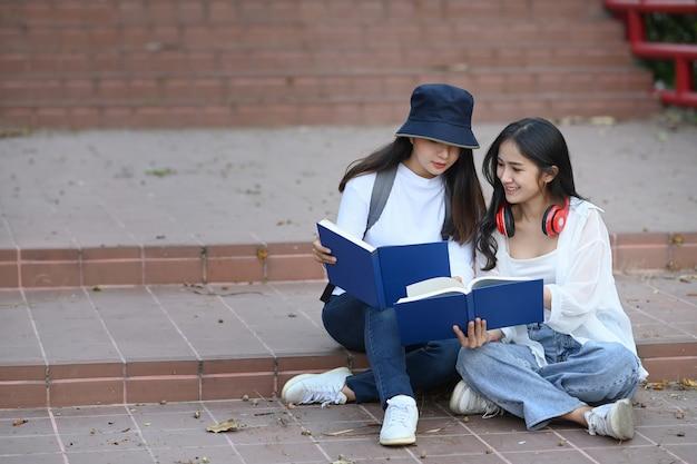 Studenti che leggono un libro interessante e si preparano per l'esame seduti insieme nel campus.