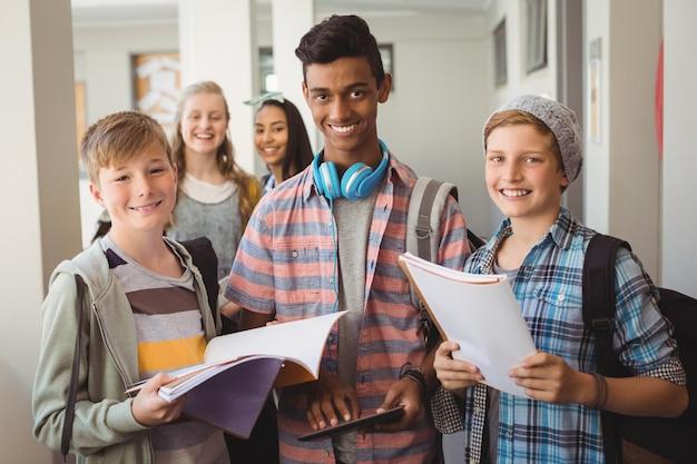 Studenti in piedi con notebook e tavoletta digitale in corridoio