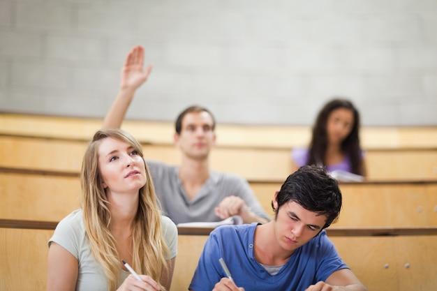 Gli studenti prendono appunti mentre il loro compagno di classe sta alzando la mano
