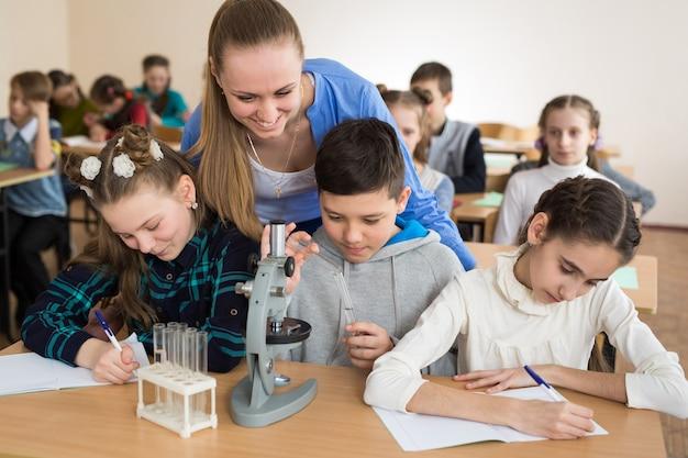 Studenti che usano bicchieri di scienze e un microscopio alla scuola elementare
