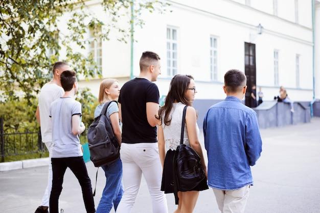 Studenti che camminano insieme vicino all'edificio bianco, vista dal retro