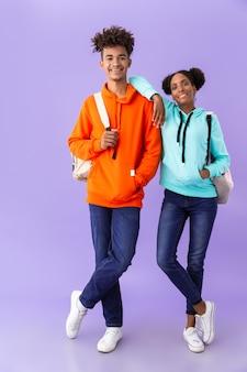 Studenti che indossano zaini che abbracciano insieme, isolati sopra la parete viola