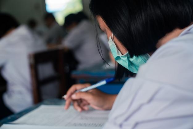 Gli studenti che indossano la maschera per proteggere il virus corona o il covid-19 e che fanno i fogli di risposta agli esami si esercitano in aula con stress.