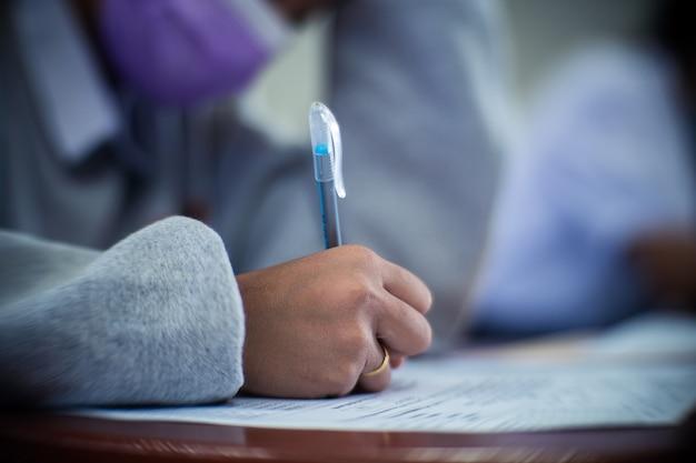Studenti che indossano una maschera per proteggere il covid-19 e fanno l'esame in classe con stress