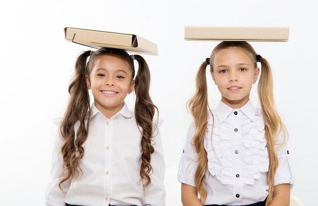 Studi e apprendimento. le ragazze felici dei bambini tengono le cartelle di file sulla testa. gli studi e l'apprendimento dei bambini si godono la giornata scolastica.