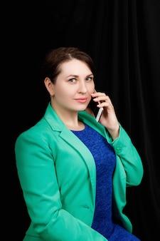 Studio close up ritratto di una ragazza di aspetto slavo indossava una camicetta blu e una giacca blu-verde su uno spazio nero parlando per telefono.