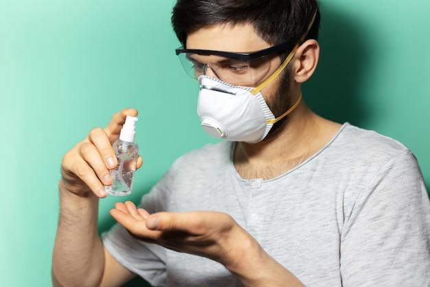Ritratto del primo piano dello studio del giovane ragazzo che utilizza il coronavirus di prevenzione del gel antisettico disinfettante