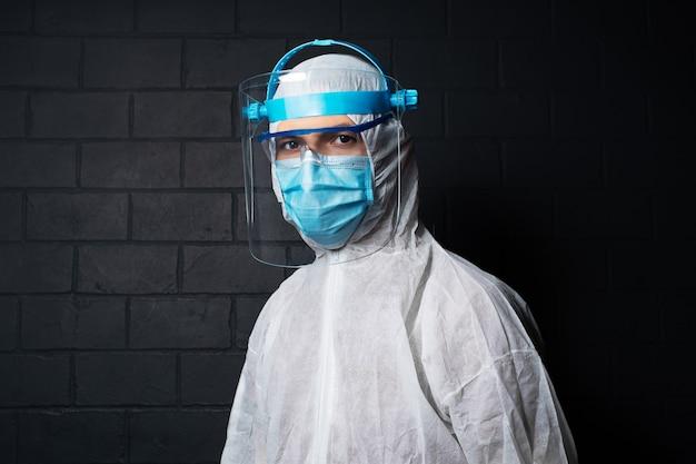 Studio ritratto scuro di giovane medico che indossa la tuta dpi contro il coronavirus e il covid-19. muro di muro di mattoni neri.