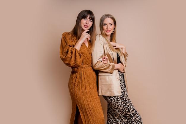 Studio fotografico di moda di due eleganti modelli in elegante autfit autunnale in posa su un muro beige
