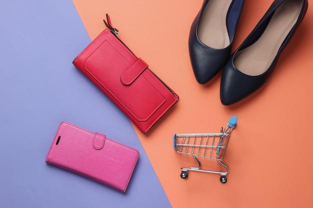 Studio fashion shot shopping concept scarpe con tacco alto rosso smartphone portafoglio nel carrello della spesa custodia in pelle