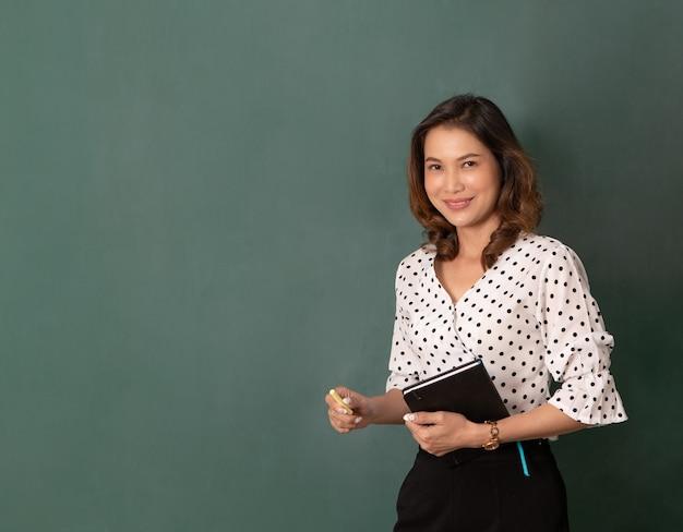 Studio colpo di luce flash, bella donna asiatica che tiene libro e gesso in piedi di fronte a una lavagna nera con spazio per le copie.