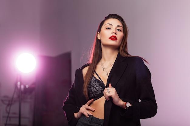 Studio fresco ritratto giovane donna attraente con gonfie labbra rosse sexy con lunghi capelli castani in reggiseno di pizzo di moda in elegante cappotto nero in studio con luce intensa. bella modella sensuale d'affari