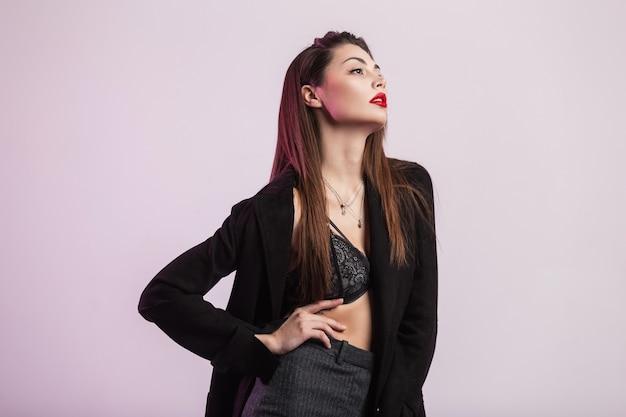 Studio fresco ritratto giovane donna bruna con pelle pulita sana con belle labbra rosse gonfie in elegante giacca nera in reggiseno di pizzo al chiuso. modello di moda ragazza sexy alla moda nella stanza vicino al muro.