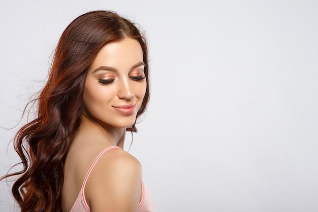 Studio glamour ritratto di una bella donna con i capelli lussuosi su uno sfondo chiaro. posto per copyspace.