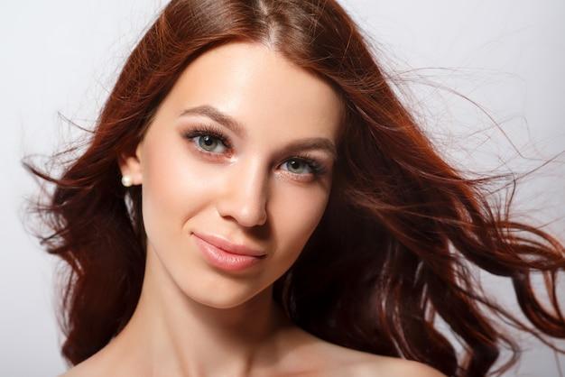 Studio glamour ritratto di una bella donna con i capelli lussuosi su uno sfondo chiaro.
