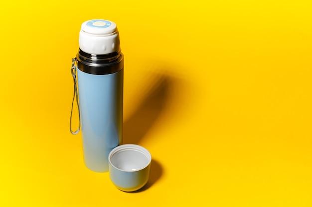 Immagine dello studio di thermos blu-chiaro con cappuccio di colore giallo con lo spazio della copia.