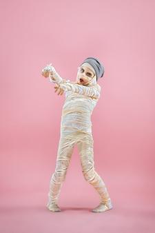 Immagine dello studio di una giovane ragazza adolescente fasciata, su sfondo rosa. tema di halloween insanguinato: lo sfondo dello studio pazzo maniaco