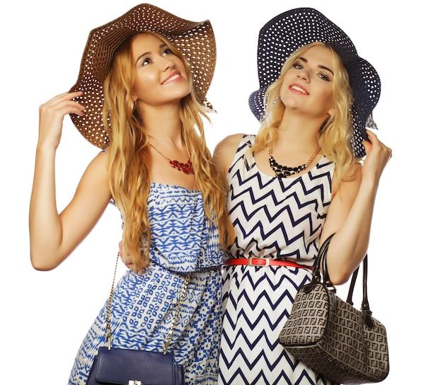 Studio lifestyle ritratto di due migliori amiche ragazze che indossano eleganti abiti estivi e cappelli di paglia, che si divertono insieme. isolato su bianco.