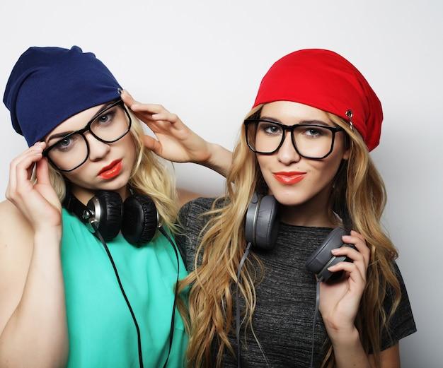 Studio lifestyle ritratto di due migliori amiche hipster che indossano abiti eleganti e luminosi, cappelli, pantaloncini di jeans e occhiali, impazziscono e si divertono insieme. giovani e bellezza.