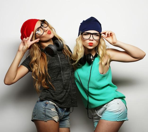 Ritratto in studio lifestyle di due migliori amiche hipster che indossano abiti eleganti e luminosi, cappelli, pantaloncini di jeans e occhiali, impazziscono e si divertono insieme