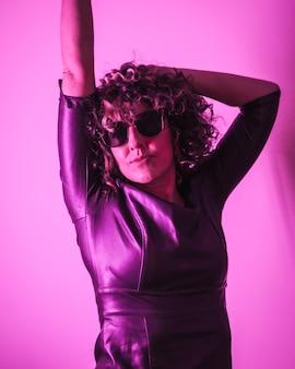 Stile di vita da studio, una giovane donna caucasica che si diverte molto in una sessione fotografica con abiti eleganti e occhiali da sole, con luce rosa al neon