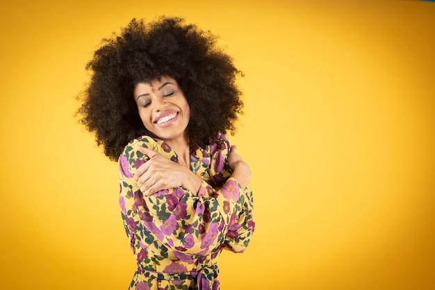 Foto di studio di una giovane e affascinante donna afroamericana in un elegante pantaloni blu che ha soddisfatto la felice espressione del viso,